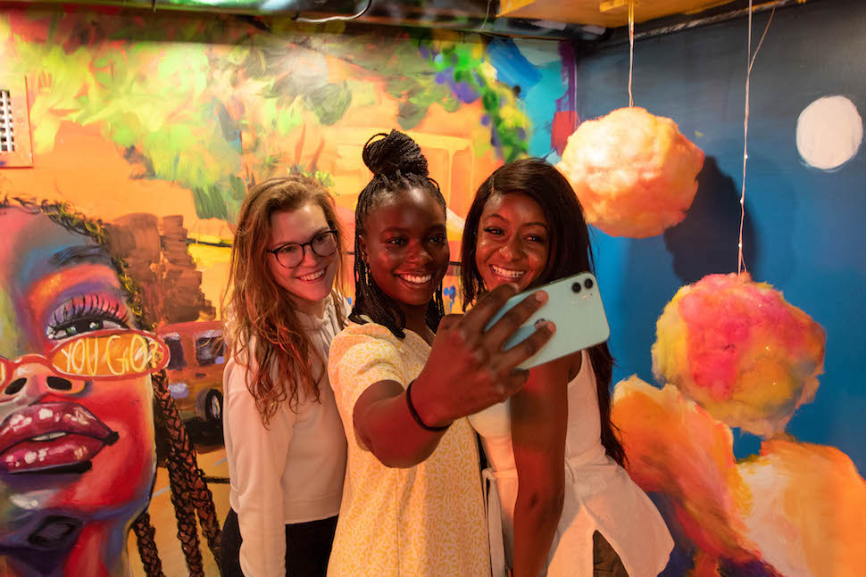 Three girls taking selfie in front of artwork