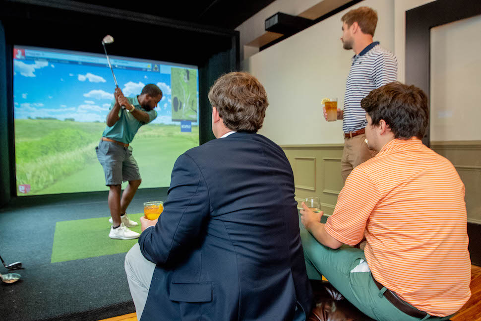 Four men with drinks in golf swing simulator