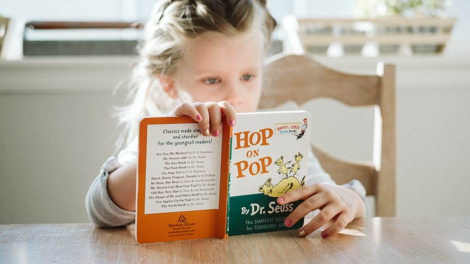 Young girl reading Dr. Suess book