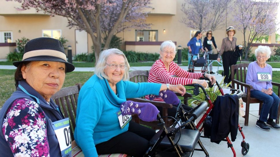 Senior women with walkers and numbered race bibs