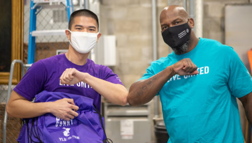 """United Way volunteers elbow-bumping in matching """"Live United"""" t-shirts"""