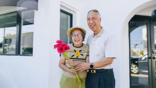 Senior couple smiling and holding flowers