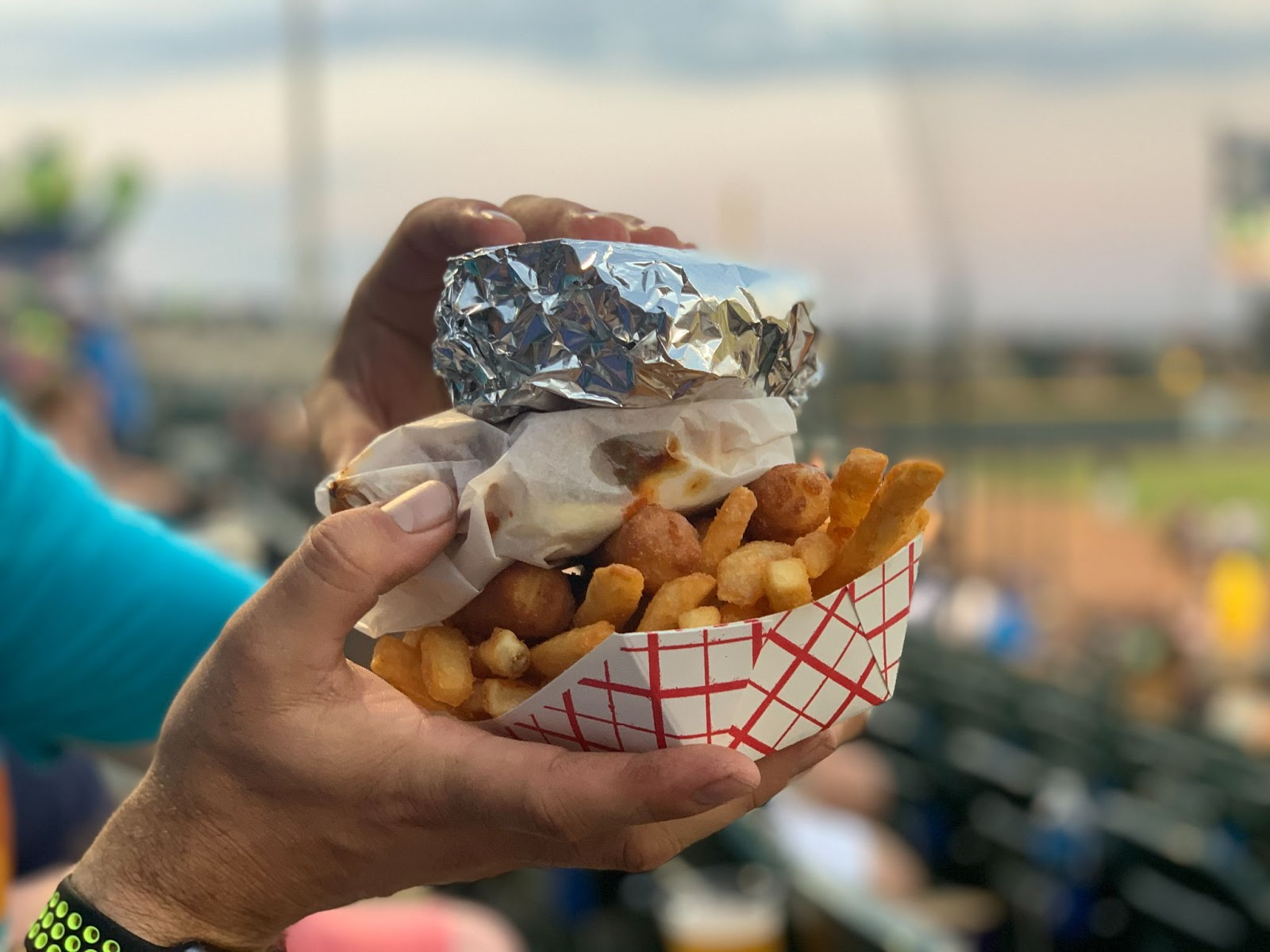 Hands holding french fries topped with more snacks