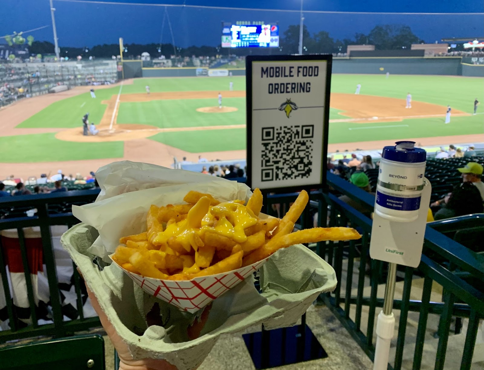 Cheese fries in front of mobile ordering sign