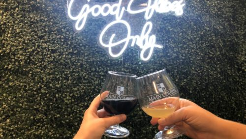 """Beer glasses clinking together in front of green leafy backdrop featuring a """"Good Vibes Only' neon sign"""